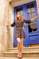 Pretty tall slim young girl in short dark dress with small flowers posing near blue door, long blond hair tender face long legs photo
