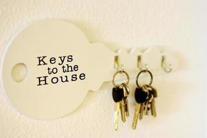 Manojo de llaves colgando de un soporte en una pared blanca, llavero de madera en la pared de luz foto