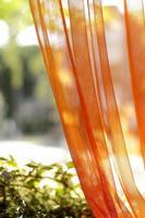 la luz del sol se extiende a través de la cortina de tul naranja foto
