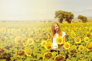 Smiling young woman in field sunflowers, farming time in countryside photo