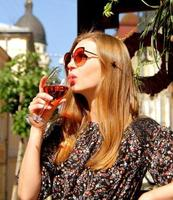 Young woman in sunglasses drinking glass of pink red wine outdoor in cafe, long blond hair dark dress photo