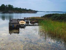 Rowing boat moored at a small jetty in the Baltic Sea near Mariehamn Aland Finland photo