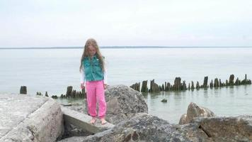Girl plays over large stones on the seashore video