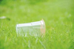 Closeup clear plastic cup garbage recycles on the green grass field in the park with the nature of the freshness of the grass. Concept cleanliness photo