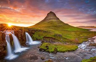 Amazing sunset the top of Kirkjufellsfoss waterfall with Kirkjufell mountain in the background on the north coast of Iceland's Snaefellsnes peninsula taken white a long shutter speed. photo