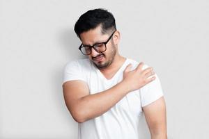 Apuesto joven con gafas negras con dolor en el hombro sobre fondo blanco. foto