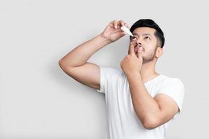 Medicina de la visión y oftalmología, concepto de salud, retrato de vista lateral de un joven apuesto con camiseta blanca aplicando gotas para los ojos sobre fondo blanco foto