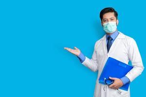 Doctor en bata de laboratorio sosteniendo el archivo del paciente o notas médicas mirando a la cámara, aislado en el espacio de copia de fondo blanco foto