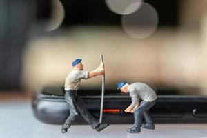 Trabajador de personas en miniatura con herramientas de reparación de teléfonos móviles foto