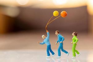 Gente en miniatura familia feliz corriendo y jugando con globo. foto