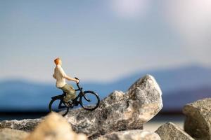 Viajero de personas en miniatura con bicicleta en la roca foto