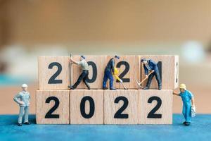 El equipo de trabajadores de personas en miniatura crea un bloque de madera número 2022 foto