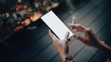 manos de mujer y smartphone con cigarrillos. video