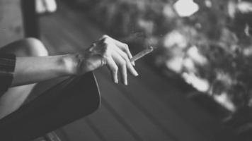 el cigarrillo en la mano de la mujer. video