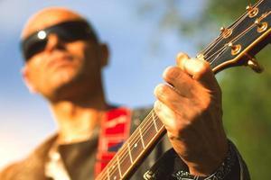 Mango de guitarra acústica con mano haciendo arreglos con el guitarrista de desenfoque foto