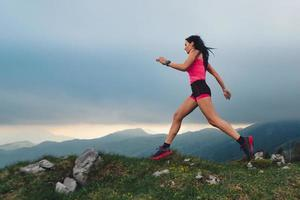 Acción de mujer deportiva con cuerpo atlético durante una carrera de naturaleza foto