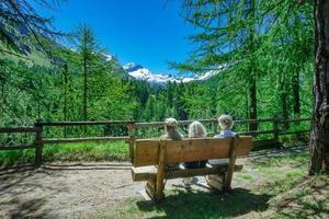 Los turistas en un banco en las montañas se relajan mientras observan la vista. foto