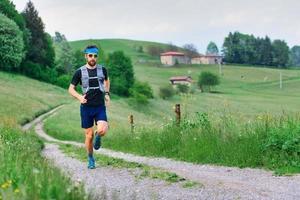 Joven atleta con barba se ejecuta en el paisaje de colinas rurales foto