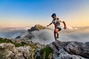 Hombre corredor de ultramaratón en las montañas que entrena al atardecer foto