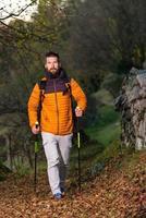 Joven con barba practicando nordic walking en camino de hojas foto