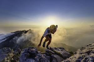 hombre corredor del cielo cuesta arriba en las rocas al atardecer foto