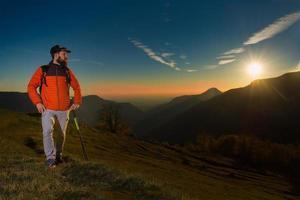 Joven con barba mirando el panorama está descansando durante una caminata nordc walking foto