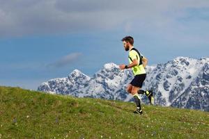 Skyrunning un hombre barbudo en un prado de primavera con fondo de montañas nevadas foto