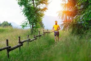 Sendero de montaña en la pradera con hombre corriendo con palos en mano foto