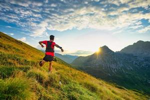 Runner skyrunner on a mountain meadow at dawn photo