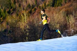 A young man athlete runs in the snow photo