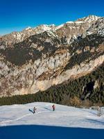 paisaje de montaña con nieve con dos excursionistas. foto
