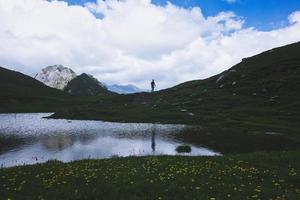 paisaje de montaña con un pequeño lago y una persona caminando foto