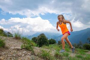 una niña practica correr por un sendero en las montañas foto