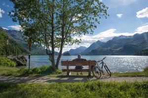 Un ciclista descansa mirando la vista en un banco frente a un lago de montaña foto