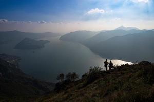 un par de excursionistas miran el panorama del lago isea en italia foto