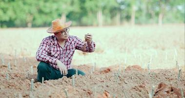 The young farmer looked at the soil in his hand video