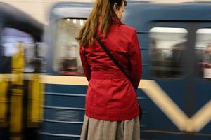 A pretty woman in a red jacket waiting for arrival of a train in the subway station photo