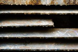 Cerca de la pared de celosía de metal oxidado, textura grunge, líneas abstractas con textura marrón, fondo aislado de construcción de hierro antiguo, superficie metálica sucia marrón, material cubierto de óxido, telón de fondo áspero foto
