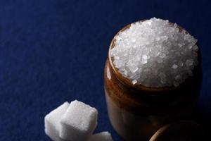 azúcar. Azúcar granulada blanca y azúcar refinada sobre un fondo azul. foto