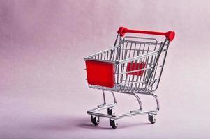 un carrito de la compra o una carretilla sobre fondo rosa foto