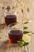 Taza de té con jengibre, limón y menta en la mesa de madera foto