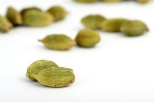 Cardamom pods on white background photo