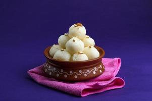 Indian Sweet or Dessert - Rasgulla, Famous Bengali sweet in clay bowl with blue napkin on violet background photo