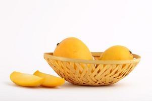 Fruta de mango en la canasta con rodaja sobre fondo blanco. foto