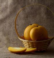 Fruta de mango en la canasta sobre fondo de tela de saco foto