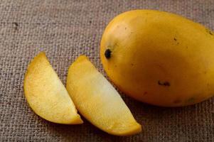 Fruta de mango con rodaja sobre fondo de tela de saco foto