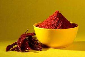 chili powder in yellow bowl on yellow background. Red chilly pepper photo