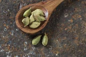 Cardamom pods in wooden spoon on a textured background photo