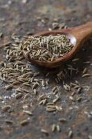 Cumin seeds in wooden spoon on a textured background photo