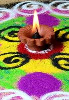 Clay diya lamps lit during diwali celebration, Rangoli in background photo